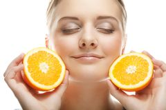 Женщина с апельсинами в ее портрете студии рук изолированном на whit стоковая фотография