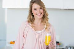 Женщина с апельсиновым соком в кухне Стоковые Изображения RF