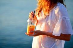 Женщина с апельсиновым соком в устранимой чашке против моря Стоковое Изображение RF