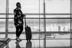 Женщина с багажом в аэропорте ждет самолет стоковая фотография