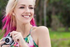 Женщина с белокурыми и magenta розовыми волосами используя камеру Стоковые Фотографии RF