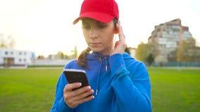 Женщина с беспроволочными наушниками и smartphone выбирает музыку и бежит через стадион на заходе солнца