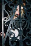 Женщина с белокурым вьющиеся волосы за загородкой Стоковое Фото