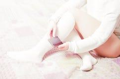 Женщина с белыми чулками в кровати Стоковое Изображение