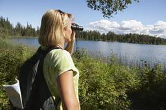Женщина с биноклями на озере Стоковое фото RF