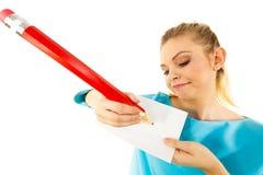 Женщина с большим сочинительством карандаша на бумаге Стоковые Изображения RF