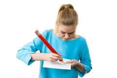 Женщина с большим сочинительством карандаша на бумаге Стоковые Фотографии RF