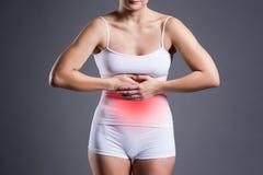 Женщина с болью в животе, stomachache на серой предпосылке Стоковое Изображение RF