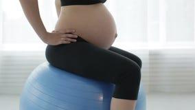 Женщина с большим животом делает тренировку сидя на шарике тренировки сток-видео