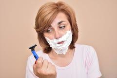 Женщина с брить пену на ее стороне держа и смотря уныло на бритве стоковая фотография