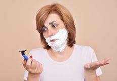 Женщина с брить пену на ее стороне держа и смотря уныло на бритве стоковые фото