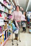 Женщина с вагонеткой покупок в аптеке Стоковая Фотография
