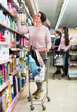 Женщина с вагонеткой покупок в аптеке Стоковые Фото