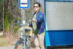 Женщина с велосипедом и корзина в автобусной остановке Стоковое фото RF