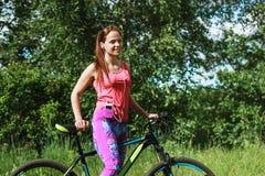 Женщина с велосипедом спорта в лесе Стоковые Фото