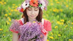 Женщина с венком на главных выборах сирени и цветках тюльпана в саде Счастливый садовник женщины с цветками Весна и лето акции видеоматериалы