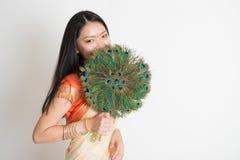 Женщина с вентилятором пера павлина в индийском платье сари Стоковое Фото