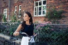 Женщина с велосипедом идя вдоль дороги Стоковые Изображения