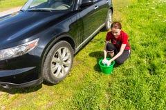 Женщина с ведром скручивая вне губку рядом с автомобилем Стоковые Фото