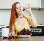 Женщина с вишнями в домашней кухне Стоковая Фотография RF