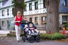 Женщина с двойной прогулочной коляской стоковые изображения rf