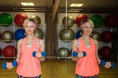 Женщина с гантелями в спортзале стоковое изображение