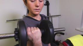 Женщина с гантелями делая тренировки для бицепсов сток-видео