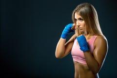 Женщина с голубыми повязками бокса, съемка фитнеса студии Космос для текста спортсмен подготавливая для удара в тренировке стоковое изображение