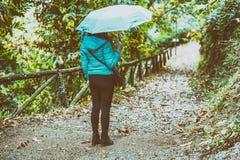 Женщина с голубым зонтиком идя на переулок горы стоковые изображения rf