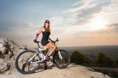 Женщина с горным велосипедом под небом на заходе солнца Стоковое Изображение RF