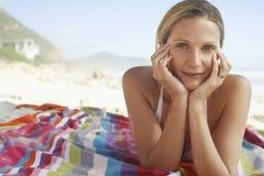 Женщина с головой в руках лежа на одеяле на пляже стоковые изображения