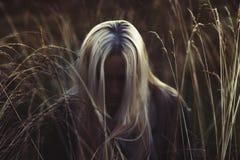 Женщина с длинными белокурыми волосами обхватывая ее голову в высокорослом поле травы в темноте стоковые изображения