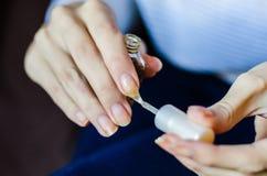 Женщина с длинными пальцами и ногтями прикладывая прозрачное основание ногтя стоковая фотография