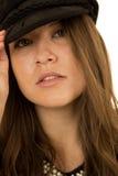 Женщина с ее рукой на черной шляпе с серьезным взглядом Стоковая Фотография RF