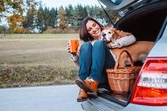 Женщина с ее собакой имеет время чая во время их trav автомобиля осени Стоковое Фото