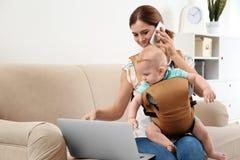 Женщина с ее сыном в несущей младенца используя ноутбук и говорить по телефону дома стоковая фотография