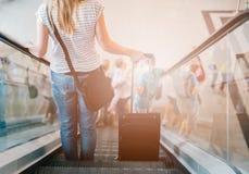 Женщина с ее чемоданом на эскалаторе Стоковые Изображения
