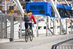 Женщина с ездами рюкзака и куртки велосипед на мосте рядом с автобусом предпочитая здоровый образ жизни стоковая фотография rf