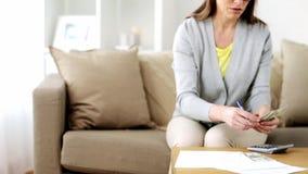 Женщина с деньгами, бумагами и калькулятором дома видеоматериал