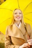 Женщина с желтым зонтиком в парке осени Стоковое Изображение RF
