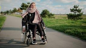 Женщина с заболеванием ног и позвоночника едет кресло-коляска в парке, усмехаясь сток-видео