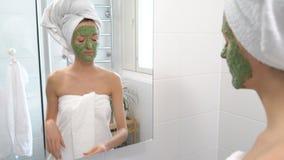 Женщина с зеленой moisturizing маской на ее стороне внезапно видит в зеркале и устрашена видеоматериал