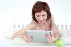 Женщина с зеленым яблоком и таблетка на кровати Стоковая Фотография RF