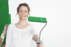 Женщина с зеленым роликом краски стоковое изображение rf
