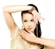 Женщина с золотистыми ногтями и красивейшими ювелирными изделиями золота Стоковое Изображение RF