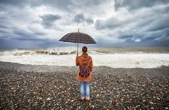 Женщина с зонтиком около бурного моря Стоковая Фотография