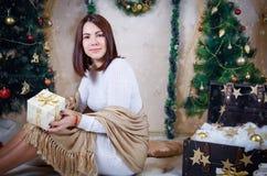 Женщина с золотым подарком под рождественской елкой Стоковое Фото