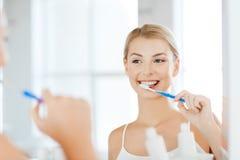 Женщина с зубами чистки зубной щетки на ванной комнате Стоковые Изображения RF
