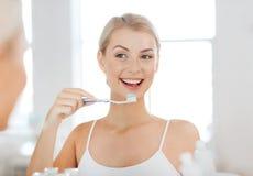 Женщина с зубами чистки зубной щетки на ванной комнате Стоковые Изображения