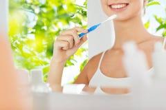 Женщина с зубами чистки зубной щетки на ванной комнате Стоковое Изображение RF